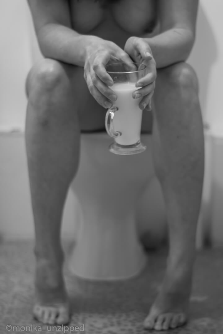 Monika sitting on the toilet with glass of milk