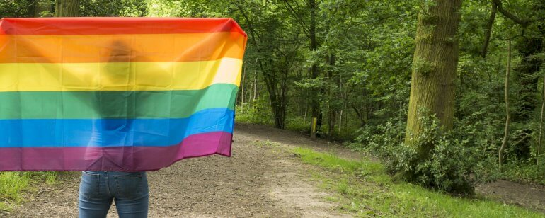 Woman holding up pride flag so that she is a silhouette behind in on woodland path
